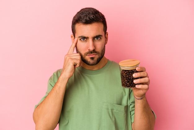 ピンクの背景に分離されたコーヒーボトルを指で寺院を指して、考えて、タスクに焦点を当てた若い白人男性。