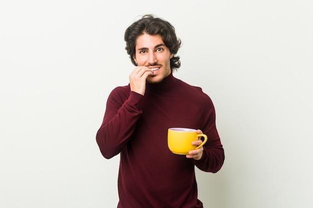 Молодой кавказский мужчина держит чашку кофе, кусая ногти, нервничает и очень тревожится.