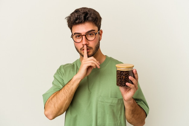 비밀을 유지하거나 침묵을 요구하는 흰색 배경에 고립 된 커피 항아리를 들고 젊은 백인 남자.