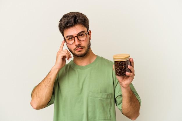 Молодой кавказский человек, держащий кофейную банку, изолированную на белом фоне, указывая висок пальцем, думая, сосредоточился на задаче.