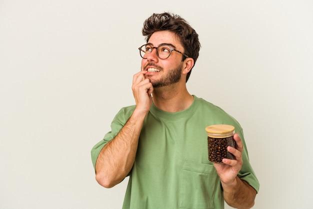Молодой кавказский человек, держащий кофейную банку, изолированную на белом фоне, расслабился, думая о чем-то, глядя на копию пространства.