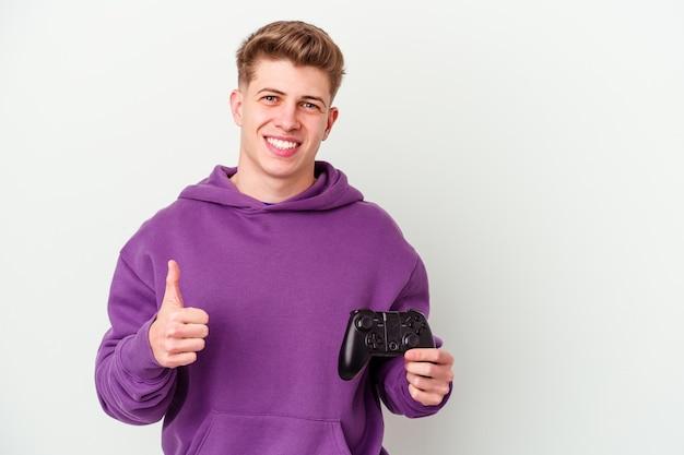 웃 고 엄지 손가락을 올리는 흰색 배경에 고립 된 게임 패드를 들고 젊은 백인 남자