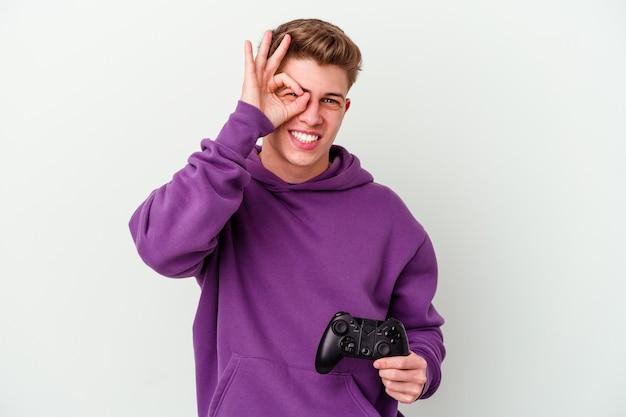 Молодой кавказский мужчина, держащий геймпад, изолированный на белой стене, взволнован, держа на глазах жест `` ок ''