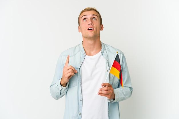 Молодой кавказский мужчина держит немецкий флаг на белом фоне, указывая вверх с открытым ртом.