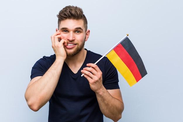 Молодой человек кавказской держит флаг германии, кусая ногти, нервный и очень тревожно.