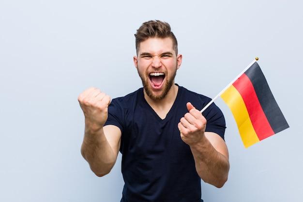 Молодой кавказский человек, держащий флаг германии, беззаботно и возбужденно аплодирует. концепция победы.