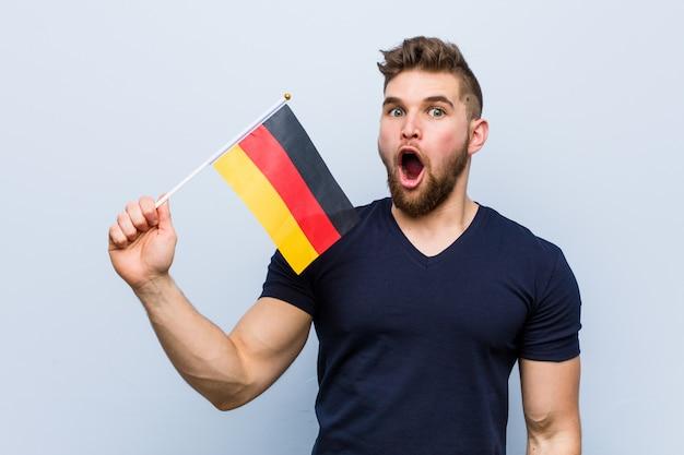 Молодой кавказский человек держа флаг германии впечатлил держащ космос экземпляра на ладони.
