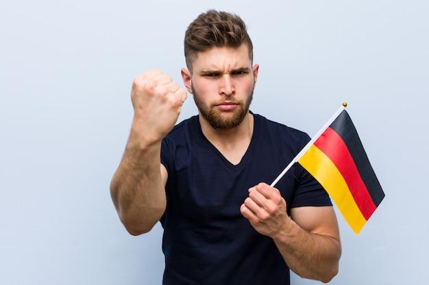 Молодой кавказский человек держа флаг германии показывая кулак к камере, агрессивное выражение лица.