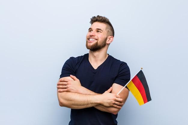 Молодой человек кавказской держит флаг германии, улыбаясь уверенно со скрещенными руками.