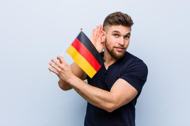 Молодой кавказский человек держа флаг германии пробуя слушать сплетню.