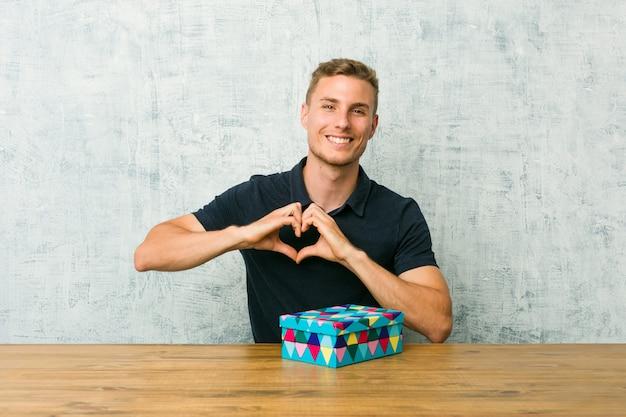 Молодой кавказский человек держа подарочную коробку на таблице усмехаясь и показывая форму сердца с руками.