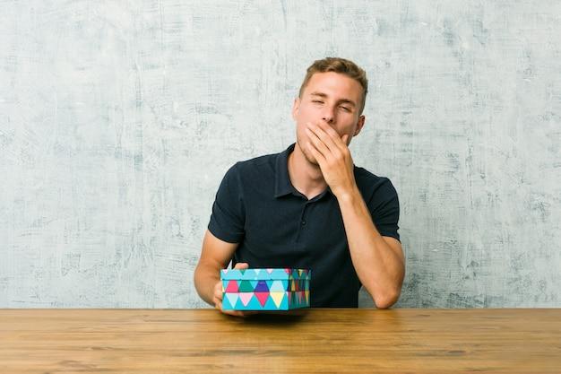 Молодой кавказский человек держа подарочную коробку на таблице зевая показывая утомленный жест покрывая рот рукой.