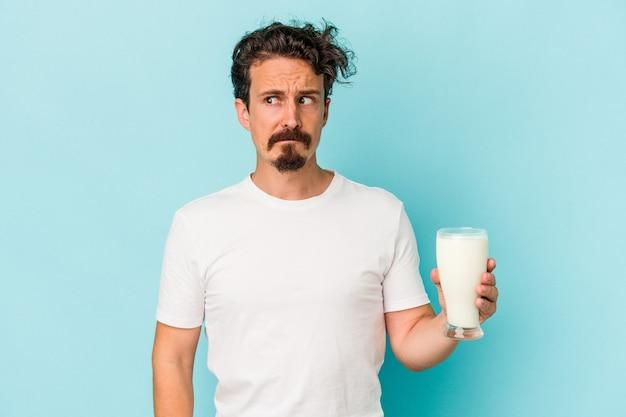 青い背景に分離されたミルクのガラスを保持している若い白人男性は混乱し、疑わしく、不安を感じています。