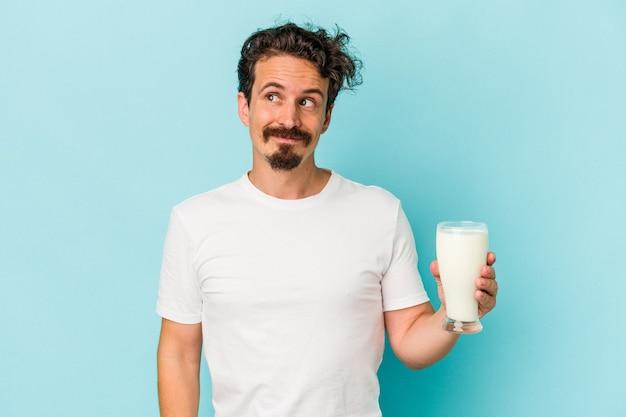 目標と目的を達成することを夢見て青い背景で隔離のミルクのガラスを保持している若い白人男性