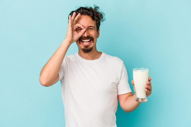 青い背景に分離されたミルクのガラスを保持している若い白人男性は、目に大丈夫なジェスチャーを維持して興奮しました。