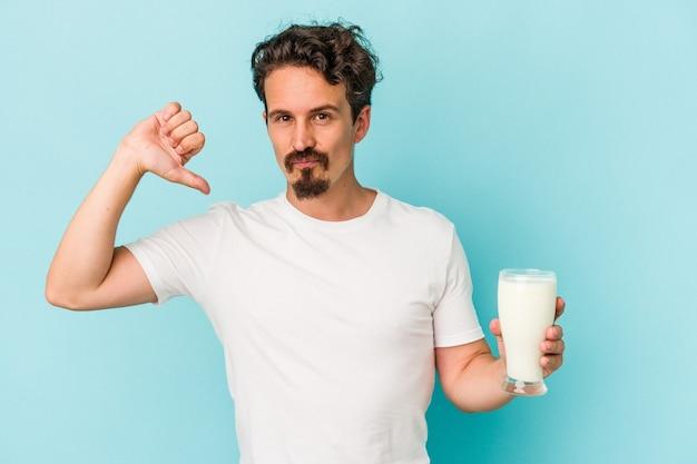 青い背景に分離されたミルクのガラスを保持している若い白人男性は、誇りと自信を持って感じます。