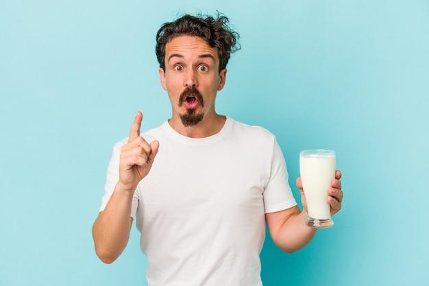アイデア、インスピレーションの概念を持っている青い背景で隔離のミルクのガラスを保持している若い白人男性。