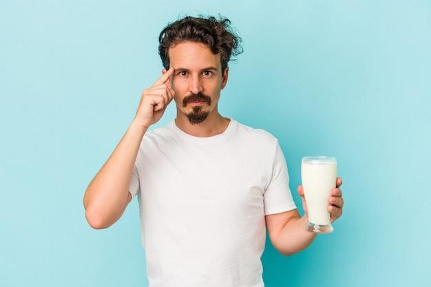 指で寺院を指している青い背景に分離されたミルクのガラスを保持している若い白人男性は、考えて、タスクに焦点を当てた。