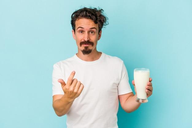 誘うようにあなたに指で指している青い背景に分離されたミルクのガラスを保持している若い白人男性が近づいています。