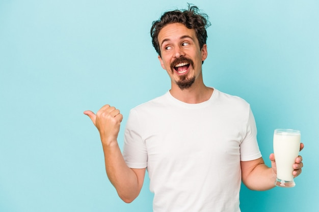 青の背景に分離されたミルクのガラスを持っている若い白人男性は、親指の指を離れて、笑ってのんきなポイントを指します。