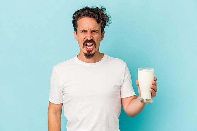 非常に怒って攻撃的に叫んで青い背景に分離されたミルクのガラスを保持している若い白人男性。