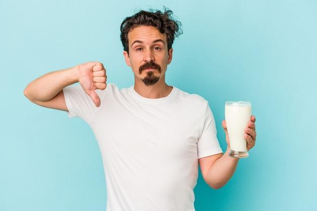 嫌いなジェスチャーを示す青い背景に分離されたミルクのガラスを保持している若い白人男性は、親指を下に向けます。不一致の概念。