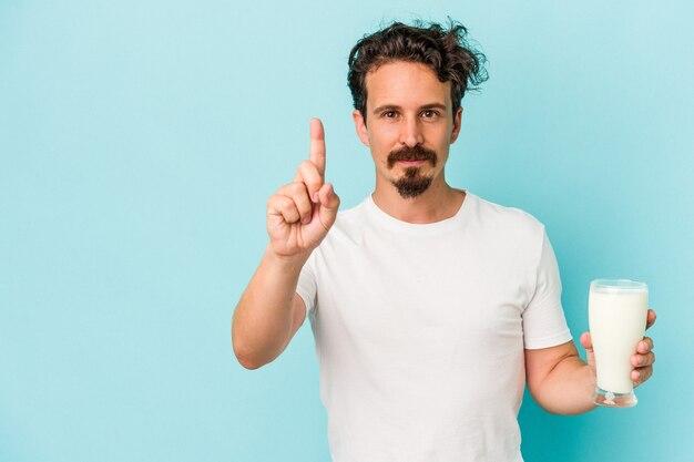 指でナンバーワンを示す青い背景で隔離のミルクのガラスを保持している若い白人男性。 Premium写真