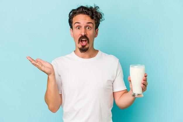 青い背景で隔離のミルクのガラスを保持している若い白人男性は驚いてショックを受けました。
