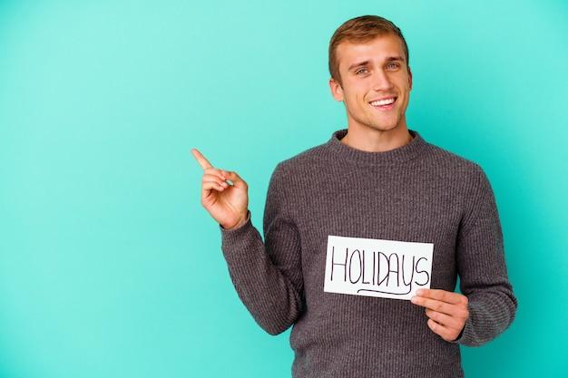Молодой кавказский мужчина держит плакат праздников, изолированных на синем, улыбаясь, весело указывая указательным пальцем.