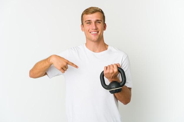 指の爪を噛んで、神経質で非常に心配している白い背景で隔離のケトルベルを保持している若い白人男性。