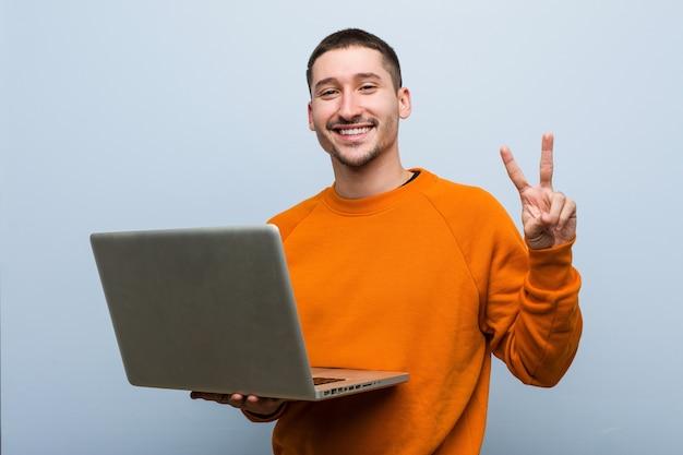 Молодой кавказский человек, держащий ноутбук, показывая номер два пальцами.