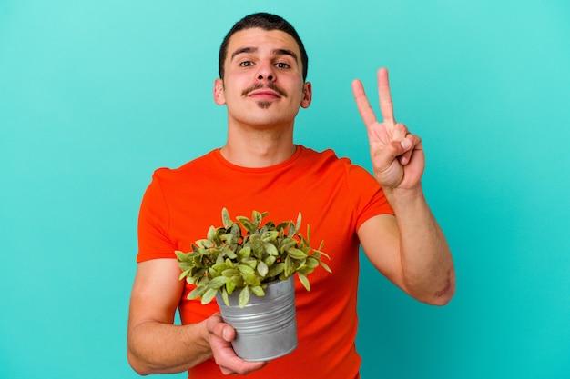 指で2番目を示す青い壁に分離された葉を保持している若い白人男性
