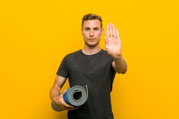 あなたを防ぐ差し出された手を示す差し出された手で立っているマットを保持している若い白人男。