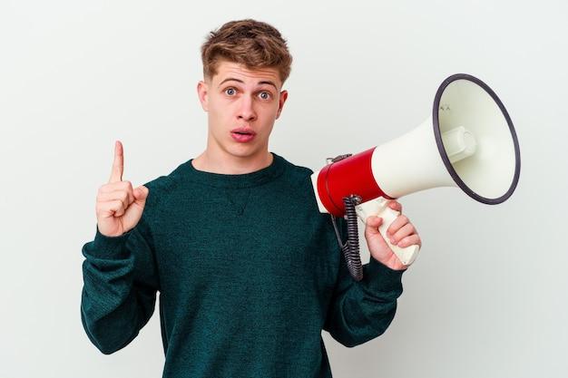 Молодой кавказский человек, держащий мегафон, изолированные на белом фоне, имея идею, концепцию вдохновения.