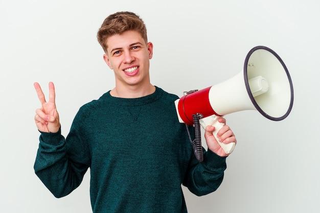 Молодой кавказский человек, держащий мегафон на белом фоне, радостный и беззаботный, показывая пальцами символ мира.
