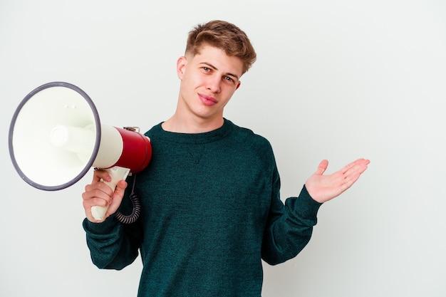 Молодой кавказский человек, держащий мегафон на белом фоне, показывает пространство для копии на ладони и держит другую руку на талии.