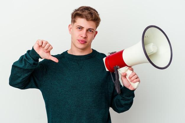 Молодой кавказский человек, держащий мегафон, изолированный на белом фоне, показывает жест неприязни, пальцы вниз. концепция несогласия.