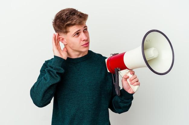 Молодой кавказский человек, держащий мегафон на белом фоне, пытается слушать сплетни.