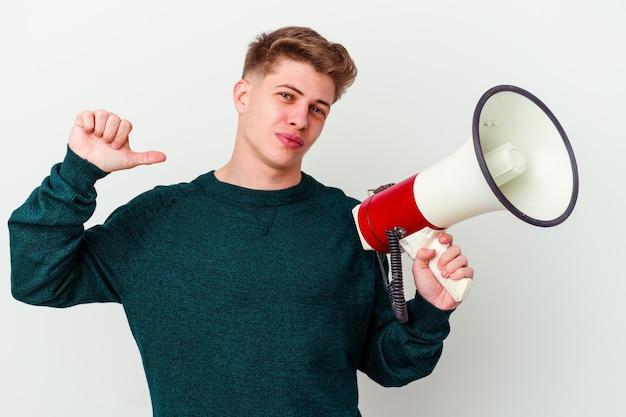 Молодой кавказский мужчина, держащий мегафон, изолированный на белой стене, чувствует себя гордым и уверенным в себе, примером для подражания.