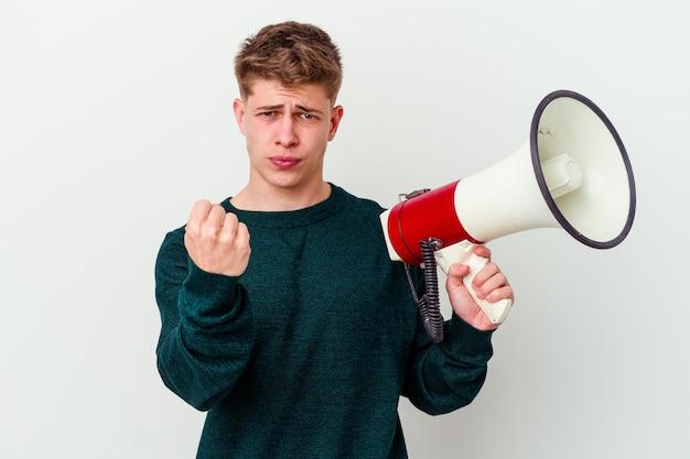 Молодой кавказский человек, держащий мегафон, изолированный на белой стене, показывает кулак на камеру, агрессивное выражение лица.