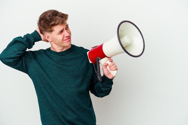 Молодой кавказский человек, держащий мегафон, изолированный на белой стене, касаясь затылка, думая и делая выбор.