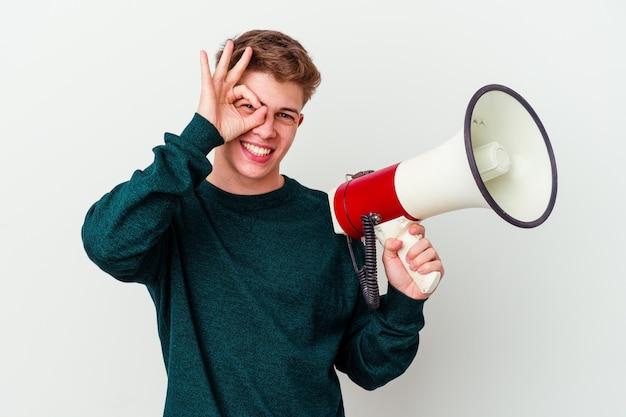 Молодой кавказский мужчина держит мегафон изолированным