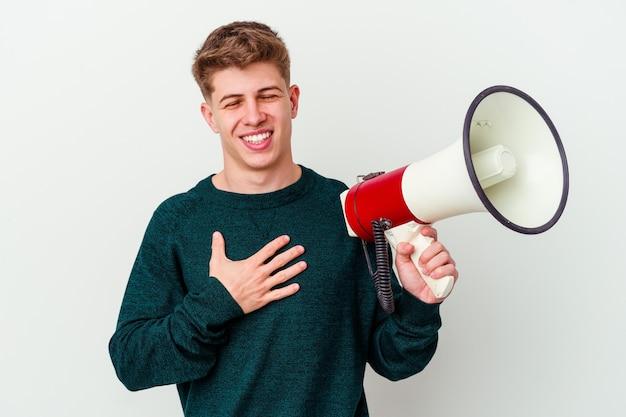 Молодой кавказский человек, держащий мегафон на белом, громко смеется, держа руку на груди.