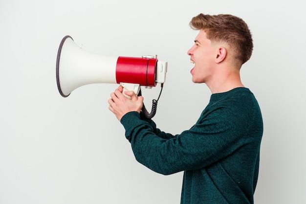 Молодой кавказский человек держит мегафон на белом кричит и держит ладонь возле открытого рта.