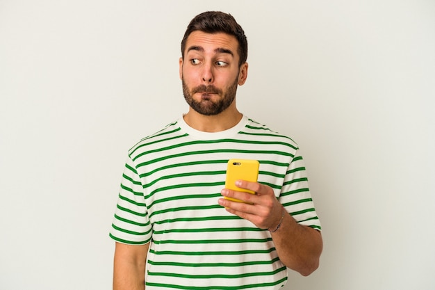 Молодой кавказский человек, держащий мобильный телефон на белом фоне, смущен, чувствует себя сомнительным и неуверенным.