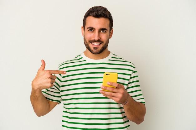 シャツを手で指している白い背景の人に分離された携帯電話を保持している若い白人男性、誇りと自信を持って