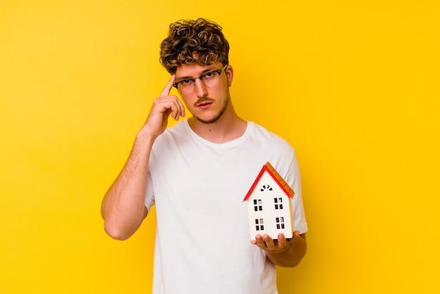 Молодой кавказский человек, держащий модельный дом, изолированный на желтом фоне, указывая висок пальцем, думая, сосредоточился на задаче.