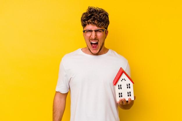 Молодой кавказский человек, держащий модельный дом, изолированный на желтом фоне, кричал очень сердито и агрессивно.