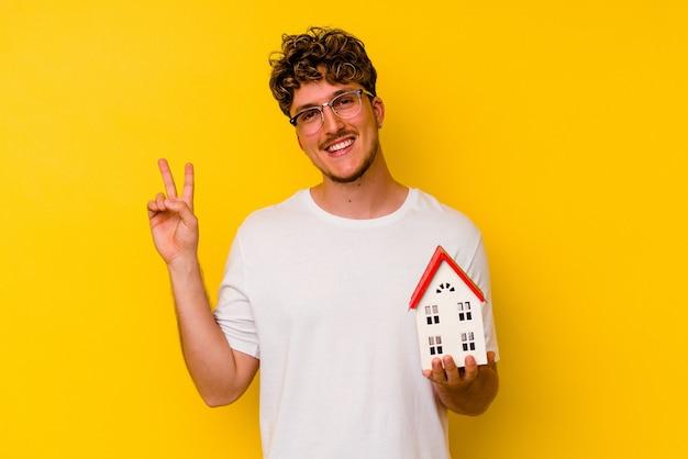 黄色の壁に隔離されたモデルハウスを持っている若い白人男性は、指で平和のシンボルを喜んで気楽に示しています。