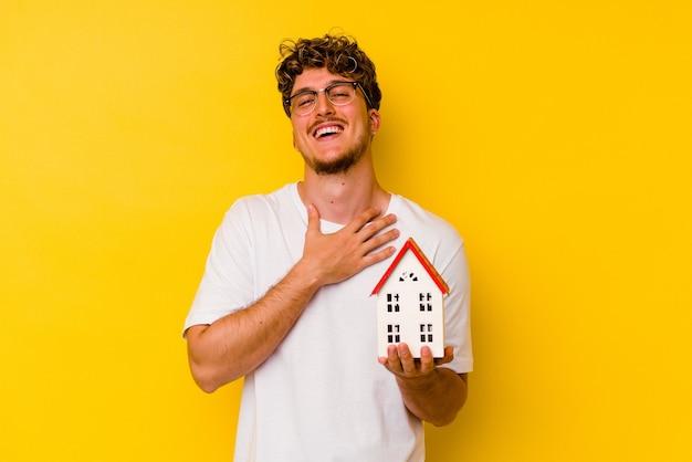 黄色い壁に隔離されたモデルハウスを持っている若い白人男性は、胸に手を置いて大声で笑います。